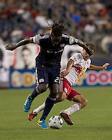 New England Revolution midfielder Shalrie Joseph (21) works to get the ball out of the defensive zone as New York Red Bulls midfielder Teemu Tainio (2) defends. On the play, Teemu Tainio earned a second yellow card and was ejected. In a Major League Soccer (MLS) match, the New England Revolution tied New York Red Bulls, 2-2, at Gillette Stadium on August 20, 2011.