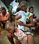 Marie Tana Desire, 27, lost her hand from injuries while she was pregnant when a concrete block fell on her during the January 12 earthquake that struck Haiti. Here, Desire holds Berthonia BiJoux, now two months old and born at Place St. Pierre camp in Petionville. Her son Frede Louis,2, is seen in the foreground on Wednesday June 23, 2010..***This is for Trenton Daniel story***.