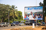 A billboard advertising Sur'Eau stands next to a busy street through Guinea's capital city of Conakry.  Sur'Eau is a chlorine product that makes water safe to drink and is distributed by the international social marketing organization, Population Services International (PSI).