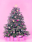 Decorated Christmas tree with presents and gift boxes isolated on pink background in pastel colors with vintage feel