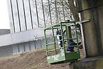 Foto: VidiPhoto<br /> <br /> DODEWAARD - Hoewel de kerncentrale van Dodewaard al ruim tien jaar volledig in ruste is (veilige insluiting), kost het gebouw nog steeds geld. Er wordt noodzakelijk onderhoud gepleegd in afwachting van de sloop in 2045. Aan de toegangsbrug naar de voormalige centrale, waar in de jaren negentig veldslagen werden uitgevochten tussen ME en demonstranten, werkt donderdag  personeel van schildersbedrijf Kuypers uit Beneden-Leeuwen om de verbinding met het gebouw in de uiterwaarde in goede conditie te houden. De brug wordt onder andere nog gebruikt door beveiligers en onderhoudsmonteurs van de centrale. Dezelfde brug moet over dertig jaar ook nog dienst doen om het puinafval van het gebouw af te voeren en wordt daarom regelmatig ge&iuml;nspecteerd. Afgelopen zomer is ook de buitenkant van de centrale nog deels in de verf gezet. De kerncentrale van Dodewaard was tussen 1969 en 1997 in bedrijf. In 2003 werd de laatste splijtstof uit de centrale afgevoerd. Beheerder GKN (Gemeenschappelijke Kernenergiecentrale Nederland) is verantwoordelijk voor de ontmanteling in 2045. Bijgebouwen en ventilatieschacht zijn al eerder afgebroken.