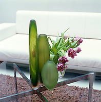 A collection of acid green glass vases is displayed next to a simple flower arrangement on a steel and glass coffee table
