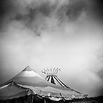 Monochrome Holga carnival image of tent tops and clouds