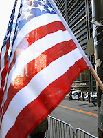 USA. New York City. Occupy Wall Street (OWS) is a people-powered movement that began on September 17, 2011 in Liberty Square in the Wall Street financial district of Manhattan. The protesters have created a small campsite at the Zuccotti Park site. OWS and has spread to over 100 cities in the United States and actions in over 1,500 cities globally. OWS is mainly protesting social and economic inequality, corporate greed, corruption and influence over government&mdash;particularly from the financial services sector&mdash;and lobbyists.  It is fighting back against the corrosive power of major banks and multinational corporations over the democratic process, and the role of Wall Street in creating an economic collapse that has caused the greatest recession in generations. The protesters' slogan, &quot;We are the 99%&quot;, refers to the difference in wealth and income growth in the U.S. between the wealthiest 1% and the rest of the population. OWS aims to expose how the richest 1% of people are writing the rules of an unfair global economy that is foreclosing on our future. OWS has being organized using a non-binding consensus based collective decision making tool known as a &quot;people's assembly&quot;. Police and american flag. 22.10.2011 &copy; 2011 Didier Ruef