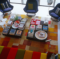 Aerial view of a pair of low coffee tables covered with piles of books on a large geometric patterned rug in the living room