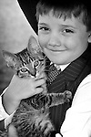 A young cowboy holding a farm cat focus on the boys eyes
