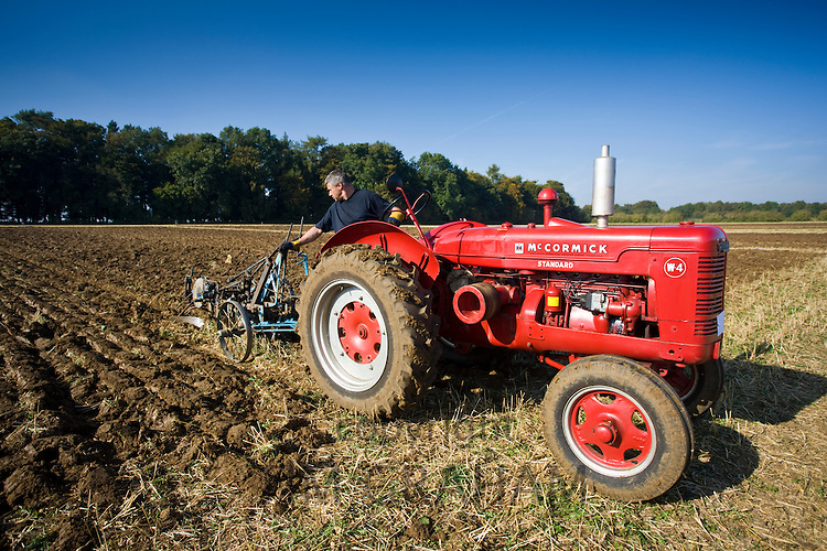 Farmer ploughing with McCormick 1943 standard tractor in country show at Great Barrington, Gloucestershire