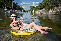 Beautiful Young Austin Woman floating in water at Barton Springs Pool, enjoying vacation at Zilker Park in Austin, Texas.