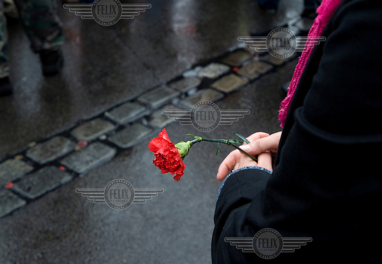 A woman holds a single red carnation at a May Day demonstration by the DGB (Confederation of German Trade Unions) in Berlin.