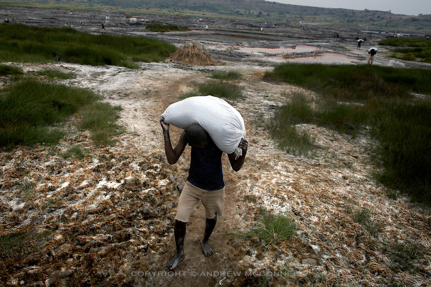 100 kg sacks of salt are carried to waiting trucks at Lake Katwe, Uganda.