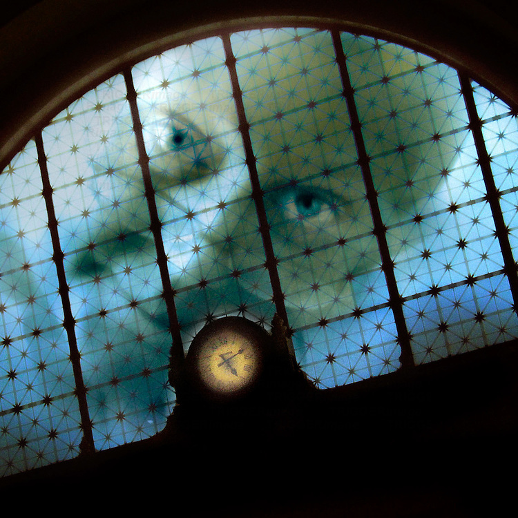 A close up of a face looking through a window with a clock face