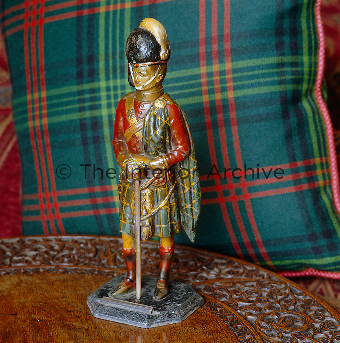 Detail of a wooden model soldier in front of a tartan cushion