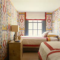 The walls of this small guest bedroom are covered in vintage ikat from Uzbekistan