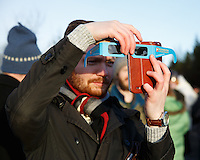 Member of the  neo-pagan Asatru association taking pictures of the solar eclipse with his mobile phone in Reykjavik, Iceland.