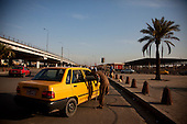 BAGHDAD, IRAQ: Hussein hales a taxi in Baghdad...On January 22nd, 2012, an IED (Improvised Explosive Devise) detonated near an Iraqi Army base in Fallujah. Hussein Jamil Abdullah, a 28 year-old soldier from Baghdad was nearby when the explosive discharged, knocking him to the ground. Hey lay there for half an hour, his right leg in an jerry-rigged tourniquet made from a headscarf, before he was taken to hospital...Gangrene set in almost immediately and the doctors at Fallujah General Hospital had to amputate his leg. He was then moved to Adnan Hospital, the military medical center, but the care Hussein received was terrible. His bandage wasn'.t changed for two days and fearing that gangrene would set in a second time his family moved him to Kerkh Hospital, which they had to cover the costs themselves, as the army refused to pay...As soon as he was wounded, the Army cut Hussein.s salary in half: from $500 a month to $250, which is less than he can live on. His brother, Ali, has given up his work as a barber to take care of him, and his two other brothers, Abbas and Hassan, now take care of the family...Before he was wounded, Hussein, was to be engaged to his fianc&eacute;e, Hind and he had even bought and furnished a room in preparation. But, after the explosion, Hind.'s father refused to allow them to marry, saying that they can.t do so until Hussein gets a prosthetic leg...In the summer, a selection of photographs were published online and caught the attention of an NGO worker in Baghdad who arranged for Hussein to have a prosthetic leg fitted...Once he had his prosthetic leg, Hussein married Hind.