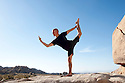 Man in the yoga pose Natarajasana outdoors balanced on a stone surface in the desert. Photography by Elena Ray Joshua Tee, CA.
