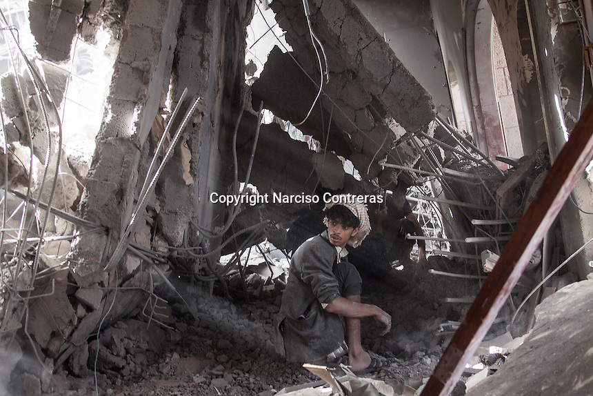 July 02, 2015 - Sana'a, Yemen: A Houthi militant reacts as he looks for survivors at the rubble of a house building after it was hit by a fighter jet belonging to the Saudi coalition in the Yemeni capital Sana'a. Two children of the family were buried and died under the rubble during the missile attack while the mother and a two other children were taken to a nearby hospital. The mother and one of the children survived the attack as another one child died by his injuries. (Photo/Narciso Contreras)