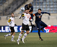 Jake Pace (20) of Maryland goes up for a header with Zach Carroll (2) and Eric Bird (11) of Virginia during the NCAA Men's College Cup semifinals at PPL Park in Chester, PA.  Maryland defeated Virginia, 2-1.