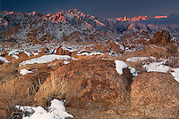 711700274 winter sunrise with snow covered granite boulders in the bureau of land management protected land the alabama hills in the southern section of the eastern sierras with lone pine peak mount whitney and mount russell in the background in kern county california
