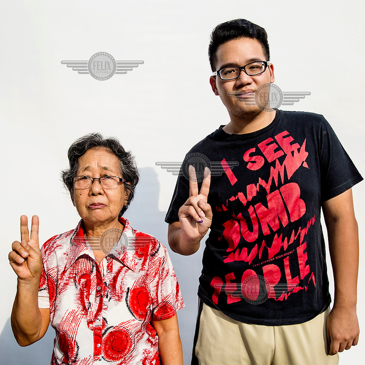 A grandmother and her grandson flash the two fingered sign symbolising Indonesian presidential candidate Jokowi's candidacy number after they cast their votes at a polling station in Jakarta.