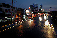 A policeman directs the traffic as the floods advance onto a major intersection in Bangkok November 4, 2011. As waterlogged Thailand struggles to contain the worst floods in decades, it faces a simple truth: not a whole lot can be done to avoid a repeat disaster in the short term even with a new multi-billion dollar water-management policy.  REUTERS/Damir Sagolj (THAILAND)