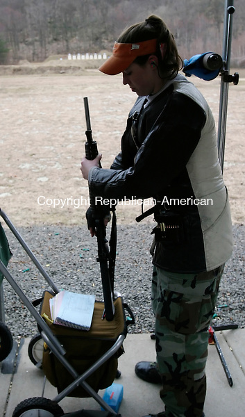 SOUTHINGTON, CT. 25 MARCH 2006- 032506BZ06- Amanda Elsenboss, 17, of Woodbury,  is silhouetted against the firing range while preparing for the  <br /> start of a competition at Bell City Rifle Club in Southington Saturday afternoon.<br /> Jamison C. Bazinet Republican-American