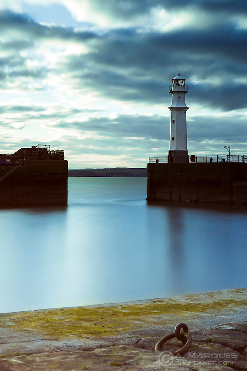 Lighthouse at the Newhaven Harbour, Edinburgh, Scotland. Long Exposure image, made from inside the harbour..Newhaven is a district of the city of Edinburgh, at the north of the city, between Leith and Granton. The lighthouse and pier are a favorite spot with local fishermen.