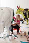 """August 9, 2012. Durham, NC.. Paula MacLeod works on """"Lady Carolina Blooo"""" who has had 125 lbs. of tile added to her 125 lbs. body..  Artists from all over the state have been working at Golden Belt decorating their assigned cows for the Parade of Cows, to be held this month. After the cows are displayed around the Triangle, they will be auctioned off to benefit the NC Children's Hospital.."""