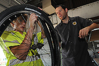 NWA Democrat-Gazette/FLIP PUTTHOFF<br /> Blake Harrison (left) shows how to repair a flat tire last Thursday July 16 2015 with help from bike-repair instructor Joel McCourt at the Greenway Bike Shop at the Jones Center in Springdale. Fixing a flat is easy and takes only minutes.