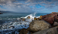 Fine Art Photograph of a seascape scene in Puerto Vallarta Mexico. The morning lighting was perfect as the long rays of the morning sun brought out the textures and details of clouds, the ocean waves crashing down onto the rocky shoreline.