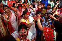 INDIA (West Bengal - Calcutta)  2006, Bengali women in the traditional dress and smeared with vermillion dancing with the bits of the drums during the immerssion cerimoney on the last day of the festival. Its a ritual of drowning the idol in the Ganges after the worship is over. Durga Puja Festival is the biggest festival among bengalies.  As Calcutta is the capital of West Bengal and cultural hub of  the bengali community Durga puja is held with the maximum pomp and vigour. Ritualistic worship, food, drink, new clothes, visiting friends and relatives places and merryment is a part of it. In this festival the hindus worship a ten handed godess riding on a lion armed wth all possible deadly ancient weapons along with her 4 children (Ganesha - God for sucess, Saraswati - Goddess for arts and education, Laxmi - Goddess of wealth and prosperity, Kartikeya - The god of manly hood and beauty). Durga is symbolised as the women power in Indian Mythology.  In Calcutta people from all the religions enjoy these four days of festival in the moth of October. Now the religious festival has become the biggest cultural extravagenza of Calcutta the cultural capital of India. Artistry and craftsmanship can be seen in different sizes and shapes in form of the idol, the interior decor and as well as the pandals erected on the streets, roads and  parks.- Arindam Mukherjee