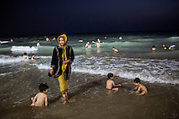 A woman paddles in the Persian Gulf. The water is full of children enjoying a night time swim.