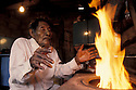 Brazil. Guarani Indian, Guató indigenous people. Elderly native warming his hands at the firewood stove. Poverty. Endangered indigenous people living in the city.