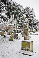 Snow covered monument and gravestones in Hampstead Parish churchyard, London, United Kingdom