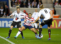 US midfielder Carli Lloyd (10) battles for the ball with German midfielders Simone Laudehr (6) and Kim Kulig (8).  The U.S. Women's National Team tied Germany 1-1 in a friendly at Toyota Park in Bridgeview, IL on October 20, 2012.