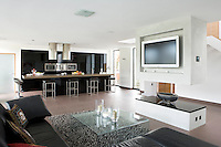 In the spacious kitchen/living area a large brown leather L-shaped sofa together with a soft tufted rug creates a cosy corner in front of the large television