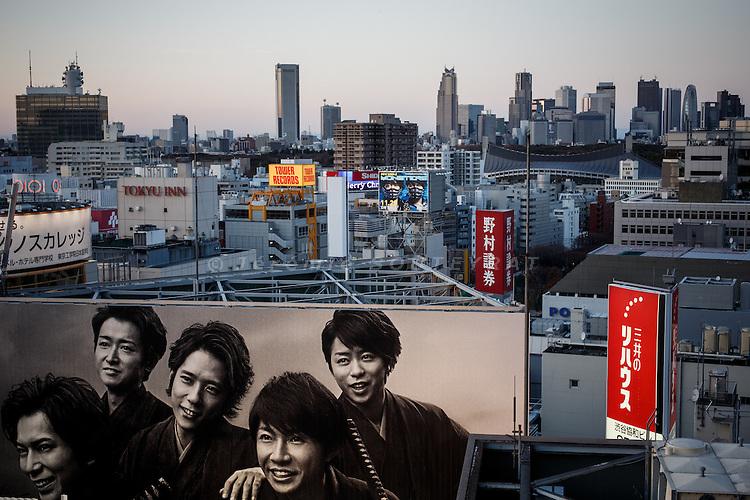 Tokyo, December 2012 - Advertising in Shibuya with Shinjuku skycrapers in the background.