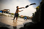 A man scoops up Mount Merapi volcanic sand that washed down the Code River from rainstorms, in Yogyakarta, Indonesia on Thursday, Nov. 11, 2010. He will sell a truck load of sand for about 30 US dollars.