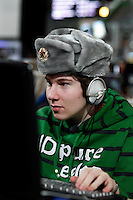 Online gamer wears a Russian military hat as he plays a game. One of the world's largest convention of computer enthusiasts, simply called 'The Gathering'. Over five thousand young people come together each Easter, some travelling long distances, each carrying their own computer equipment to the massive Vikingship sports hall in the city of Hamar. The main activity is online gaming. Many hardly see daylight or taste fresh air for the entire five days as they compete with their fellow geeks for cash prizes and the honour of being the best.