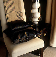 A decadent touch comes from a black buckled leather cushion on a chair in the living room