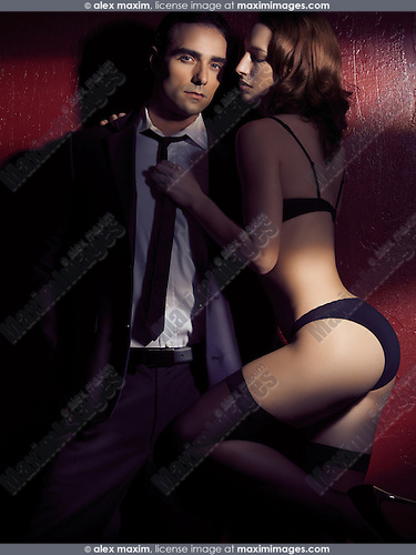 Young sexy couple, man wearing a business suit and woman in lingerie holding him by the tie in dim dramatic light