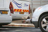 Israeli man Lying in the street at the center of Jerusalem while car are passing by. June 30, 2013. Photo By Oren Nahshon