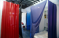 A boy's bedroom uses coloured curtains which hang from lengths of wire across the room to divide it into sleeping area, music area, etc.