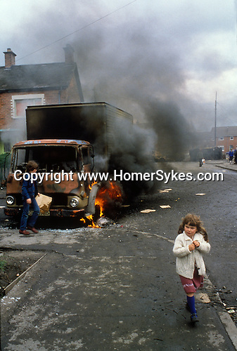 Northern Ireland The Troubles. 1980s. 1981 Burnt out hijacked lorry Belfast young children. Riots.