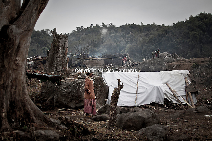 A Kachin refugee woman walks at the Je Gau Pa IDP camp, located at the high mountains of northeastern Kachin State. This camp is one of the most remote temporary shelters settled under tough and poor conditions. The camp gives shelter to two thousand displaced persona from the war-torn villages close to Maiya Jang city.