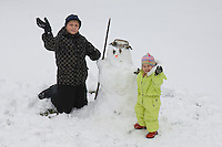 Happy Teenage Boy and Smiling Kid Girl Doing Snowman
