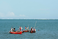 A traditional form of fishing - a group of small boats drive the fish towards a circular net fish trap.