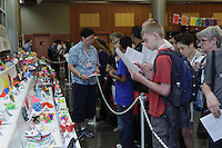OrigamiUSA 2013 attendees at the Model Menu in FIT's Great Hall selecting the folding classes they would like to attend.