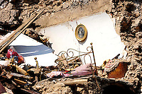 Onna  10 Aprile 2009.Terremoto Abruzzo.Macerie nelle vie del paese devastato dal terremoto , un immagine sacra rimasta appesa al muro di una casa crollata.A pile of rubble  in the main street of the devastated small village, a sacred image still hanging on the wall of a house collapsed ..