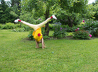 Kid turn to cartwheel in yard. Green, grass and flowerbed. Leisure activity, happy childhood. Estonia.